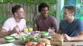 três pessoas : Three Male Friends Enjoying Meal Outdoors At Home