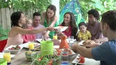 dzieci : Group Of Families Enjoying Outdoor Meal At Home