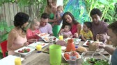 grupo de pessoas : Group Of Families Enjoying Outdoor Meal At Home
