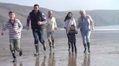 отпуск : Multi Generation Family Running On Beach In Slow Motion