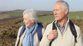 chůze : Senior Couple Walking Along Coastal Path