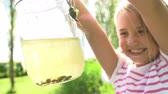 dzieci : Slow Motion Sequence Of Young Girl Holding Jar Filled With Tadpoles Wideo