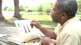dolly : Senior Man Sitting At Outdoor Table Painting Landscape Stock Footage