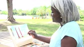 malovat : Senior Woman Sitting At Outdoor Table Painting Landscape