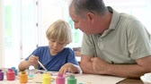 vnuk : Grandfather Painting Picture With Grandson At Home Dostupné videozáznamy