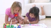dzieci : Two Girls Lying On Floor And Painting Picture At Home Wideo