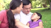 tendo : Slow Motion Sequence Of Parents Cuddling Daughter In Park