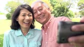клетка : Senior Asian Couple Taking Selfie In Park Together
