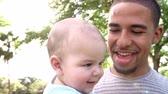 months : Slow Motion Sequence Of Father Playing With Baby Son In Park