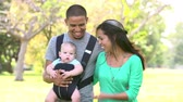 mama : Slow Motion Shot Of Family With Baby Carrier Walking In Park