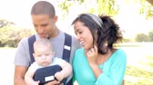 três pessoas : Hispanic Family With Baby In Carrier Walking Through Park