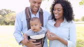 months : Family With Baby In Carrier Walking Through Park Stock Footage