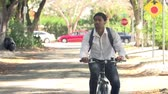 lifestyle shot : Slow Motion Sequence Of Man Cycling Along Street To Work