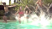 à beira da piscina : Slow Motion Shot Of Teenagers Jumping Into Swimming Pool