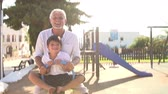 vnuk : Grandfather And Grandson On Seesaw In Playground