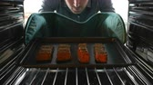 salmão : Man Putting Salmon Fillets Into Oven To Cook