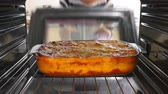 pasta dishes : Woman Taking Cooked Dish Of Lasagne Out Of The Oven