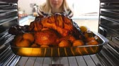 drůbež : Woman Taking Roast Turkey Out Of The Oven