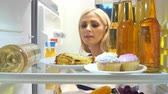 refrigerator : Woman Taking Plate Of Leftover Lasagne From The Fridge
