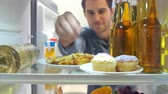 refrigerator : Man Taking Plate Of Iced Cupcakes From The Fridge