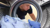 praní : Man Putting Laundry Into Washing Machine