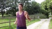 lifestyle shot : Man Running In Countryside Wearing Earphones Stock Footage