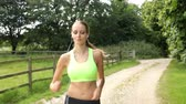 lifestyle shot : Woman Running In Countryside Wearing Earphones Stock Footage