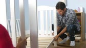 gravidez : Couple With Pregnant Wife Assembling Cot In Nursery