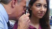 medicina : Doctor Carrying Out Ear Exam On Female Patient Stock Footage
