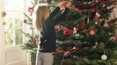 celebração : Young Girl Hanging Decorations On Christmas Tree