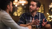 se divertindo : Two Male Friends Enjoying Evening Drinks In Bar Stock Footage