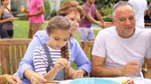 Multi Generation Family Enjoying Meal In Garden Together Stock Footage