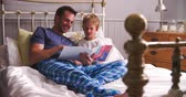 lit : Father And Son Reading Book In Bed Ensemble