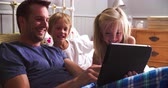 em linha : Father With Children Looking At Digital Tablet In Bed