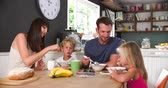 four people : Family Eating Breakfast In Kitchen Together