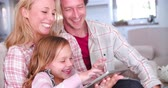 frame by frame : Family Sitting On Sofa Using Digital Tablet Stock Footage