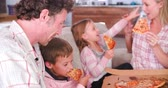 frame by frame : Family Sitting On Sofa Eating Takeaway Pizza Together Stock Footage