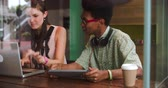 café expresso : Two Young Businesspeople Working On Laptop In Coffee Shop Stock Footage