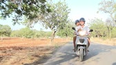 bisikletçinin : Mature Couple Riding Motor Scooter Along Country Road