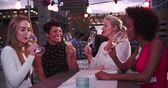 four people : Group Of Female Friends Relaxing Together At Rooftop Bar