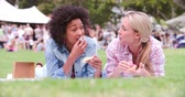 mercado : Two friends lying on the grass and eating cakes at an event Vídeos