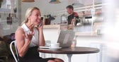 visto : Businesswoman at a table in a cafe using smartphone and laptop