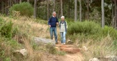 chemin : Senior couple marchant vers l'appareil photo sur le chemin rural