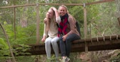 olhando para baixo : Mother and daughter sitting on a small bridge in a forest