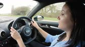 cinto : Young woman driving in a car, side view