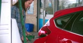 garagem : Woman refuelling a car at a petrol station