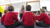 sentar se : Teacher Reading Story To Elementary School Pupils