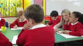writing : Pupils Working At Table With Teacher Helping Them