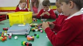 sentar se : Pupils And Teacher Working With Coloured Blocks Stock Footage