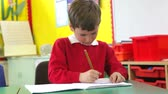 thinking : Male Pupil Practising Writing At Desk
